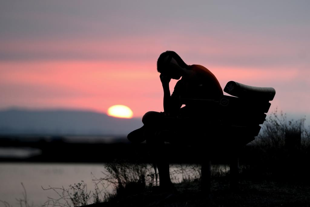 Person sitting on bench, looking downcast, with sunset in the background.