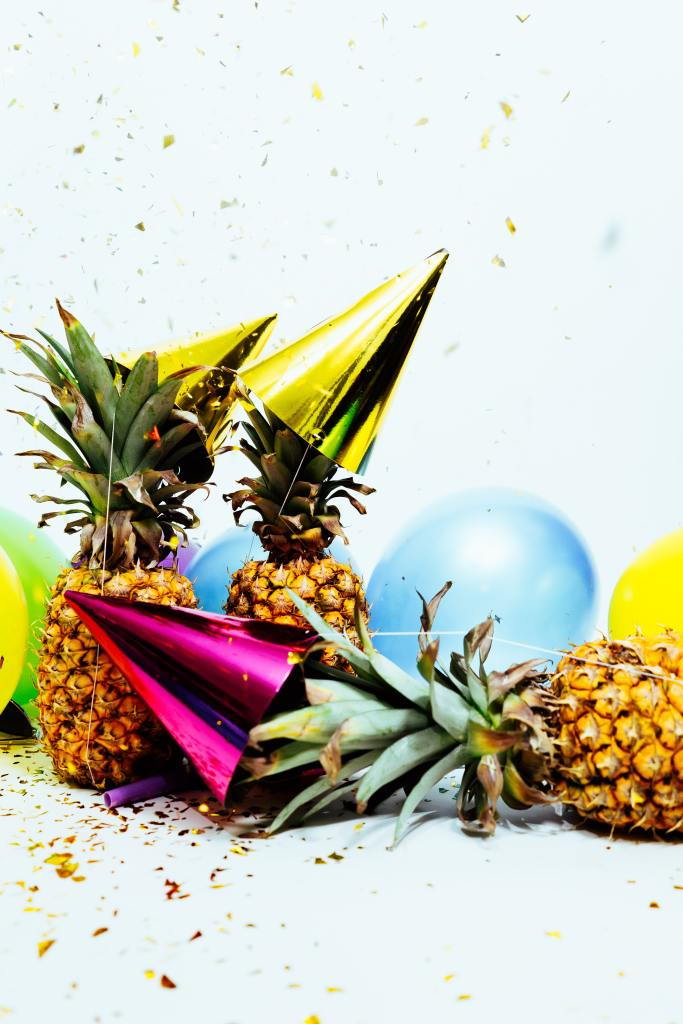 Pineapples, balloons, and party hats whimsically arranged